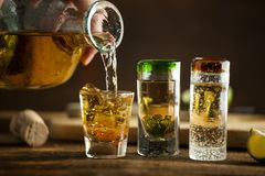 Pouring Tequila into shot glass. Selective focus. Blurred backgr Stock Photo