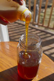 Pouring Thick Golden Honey into a Glass Container Stock Photo
