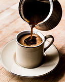 Pouring Turkish Coffee into the cup. royalty free stock photo