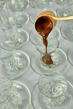 Pouring turkish coffee into traditional embossed cup. Royalty Free Stock Photo