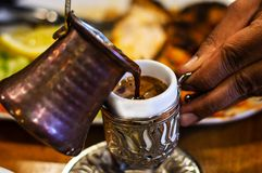 Turkish Coffee & Traditional Embossed Cup. Pouring Turkish Coffee into Traditional Embossed Metal Cup. Authentic Middle Eastern Dining stock images