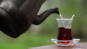 Pouring Turkish Tea to Tea Glass. With traditional teapot stock video footage