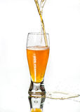 Pouring two bottles of different beers into one glass. Royalty Free Stock Photos