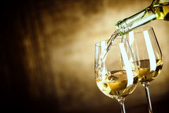 Pouring two glasses of white wine from a bottle. In a close up view of the wineglasses over an abstract brown blue background with copy space Stock Image