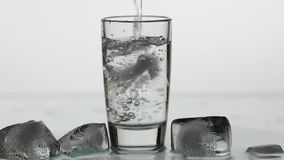 Pouring up shot of vodka into drinking glass. Slow motion. White background stock illustration