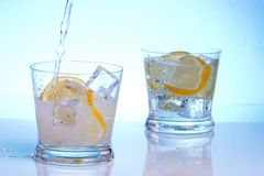 Pouring vodka into cocktails. Pouring vodka into fresh water in one of two glasses with cocktails, sliced lemon and ice cubes over aqua paper background stock photography