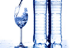 Pouring water. Pouring mineral water in a glass. Cool blue cast Royalty Free Stock Photography