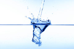 Pouring water. Blue water splash Stock Images