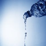 Pouring Water. Drinking water pouring from pvc bottle on blue Royalty Free Stock Photos