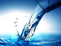 Pouring Water. Drinking water pouring from glass on blue Royalty Free Stock Photo
