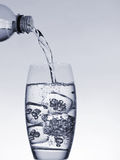 Pouring water. Water pouring into a glass Royalty Free Stock Images