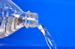 Pouring water. Fresh water bottle pouring water with blue background Royalty Free Stock Photos
