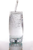 Pouring water. Mineral water poured in to a glass on a white background Stock Photography