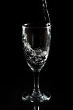 Pouring water. Into wine glass on black background Stock Photography
