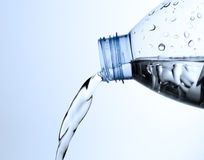 Pouring water from a bottle. In blue background royalty free stock photography