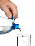 Pouring water from a bottle into a glass Stock Images
