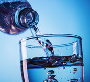 Pouring water from bottle into glass Stock Photos