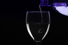 Pouring water from bottle into glass Stock Photo