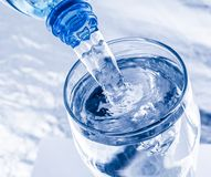 Pouring water from bottle into glass Royalty Free Stock Photo