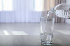 Pouring water from bottle into glass on blurred background. Space for text royalty free stock photo