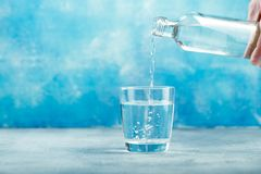 Pouring water from bottle into glass. Pouring clear water from bottle into glass on blue background royalty free stock photos