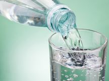 Pouring water from bottle into glass on green background royalty free stock images