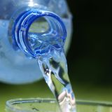 Pouring water. Close-up of bottle with pouring water. Selective focus, shallow DOF Royalty Free Stock Image