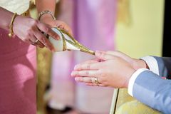 Pouring water from the conch shell into the bride hands at a T. Pouring water from the conch shell into the bride`s hands at a Thai wedding Stock Photography