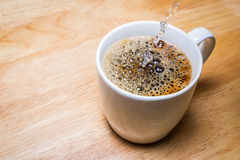 Pouring water into Cup of coffee on wooden table. focus on splash water. Stock Images
