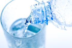 Pouring water in an elegant glass with ice and water drops. Royalty Free Stock Image