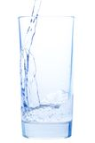 Pouring water in an elegant glass and water drops Stock Image