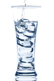 pouring water in an elegant tall glass with ice and water drops Royalty Free Stock Photo