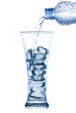Pouring water in an elegant tall glass with ice and water drops Stock Photos