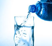 Free Pouring Water From Bottle Into Glass On Blue Background Royalty Free Stock Photo - 114978465