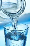 Pouring Water into a Glass. Water pouring from a jug into a glass on blue Royalty Free Stock Photos