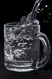 Pouring water in glass Stock Images