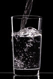 Pouring water into glass on black  background Stock Photography