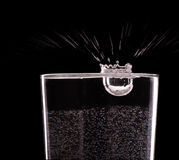 Pouring water into glass on black  background Royalty Free Stock Photo