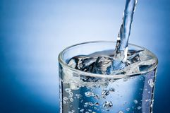 Pouring water into glass on blue background. Pouring water into glass on a blue background stock images