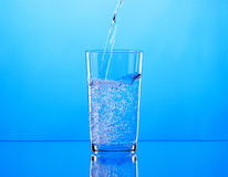 Pouring water into glass on blue background Stock Photo