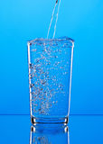 Pouring water into glass on blue background Royalty Free Stock Images