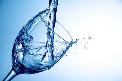 Pouring water into glass on blue background, close-up Stock Photography