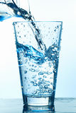 Pouring Water in the Glass With Bubbles. Pouring water with bubbles into a glass, view from the side Royalty Free Stock Photos