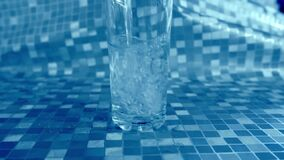 Pouring water into glass front view blue background