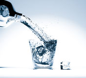 Pouring water on glass and ice cube Stock Image