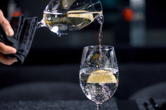 Pouring water into glass with lemon process Royalty Free Stock Images