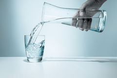 Pouring water into a glass Stock Photos