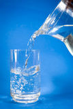 Pouring of water into glass Stock Image
