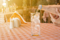 Pouring water into the glass at the restaurant table Stock Image