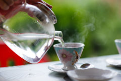Pouring water from glass teapot into a cup on a blurred background of nature Stock Images